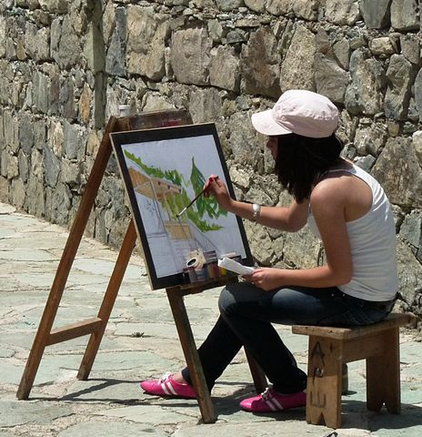 Chica pintando un cuadro al aire libre